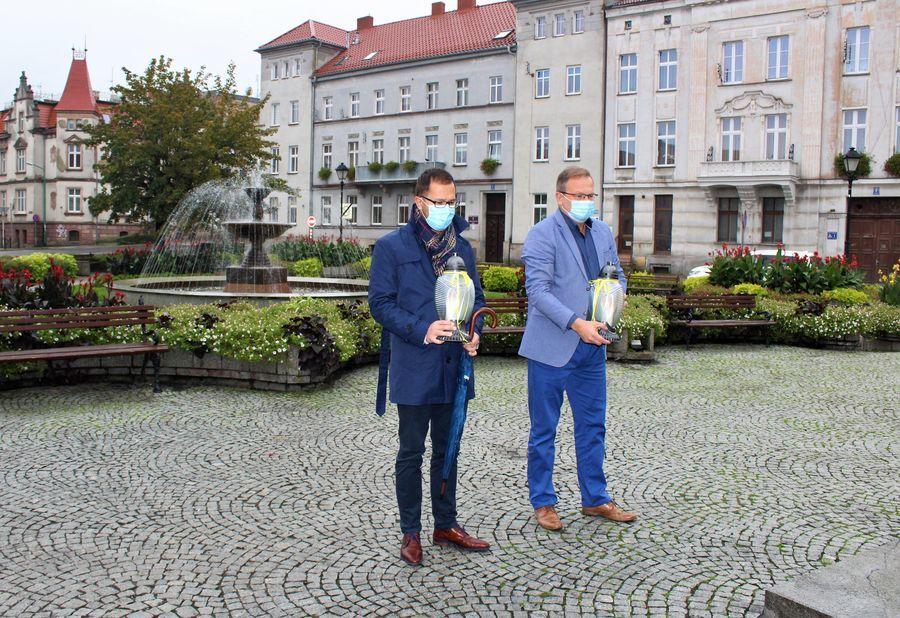 Na zdjęciu widać burmistrza miasta Pawła Ozgę i zastępcę burmistrza Tobiasza Wysoczańskiego stojących obok siebie na pl. Jana Pawła II. Obaj trzymają w ręku znicze. Za ich plecami widać fontannę.