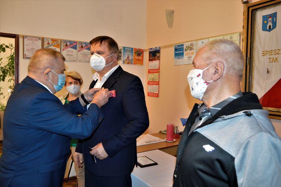 Na zdjęciu widać jak odznakę za zasługi członkowie zarządu wpinają w klapę przewodniczącego Aleksandra Jermakowa.