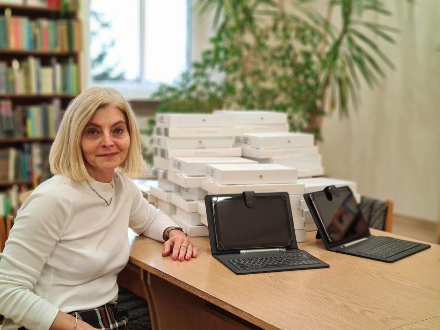 Dyrektor Zespołu Szkół Magdalena Pawiłojć siedzi przy biurku, na którym leżą otrzymane pakiety multimedialne.