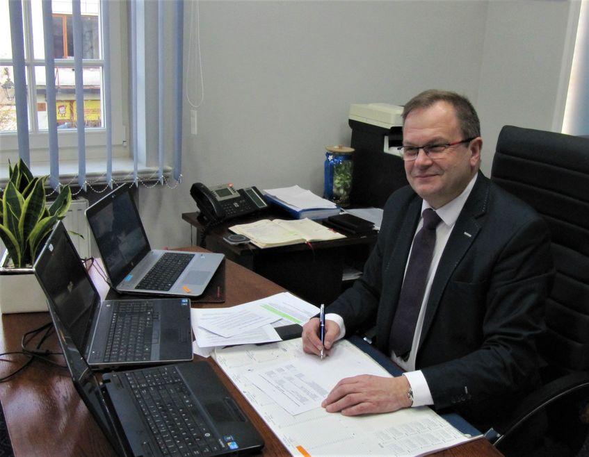 Burmistrz Miasta Paweł Ozga siedzący przy biurku na którym stoją3 komputery i leżą dokumenty