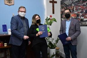 Wręczenie nagrody w konkursie Najładniejsze okno, balkon ,posesja. Zwyciężczyni nagrody wręczają burmistrz miasta Paweł Ozga i zastępca Tobiasz Wysoczański.