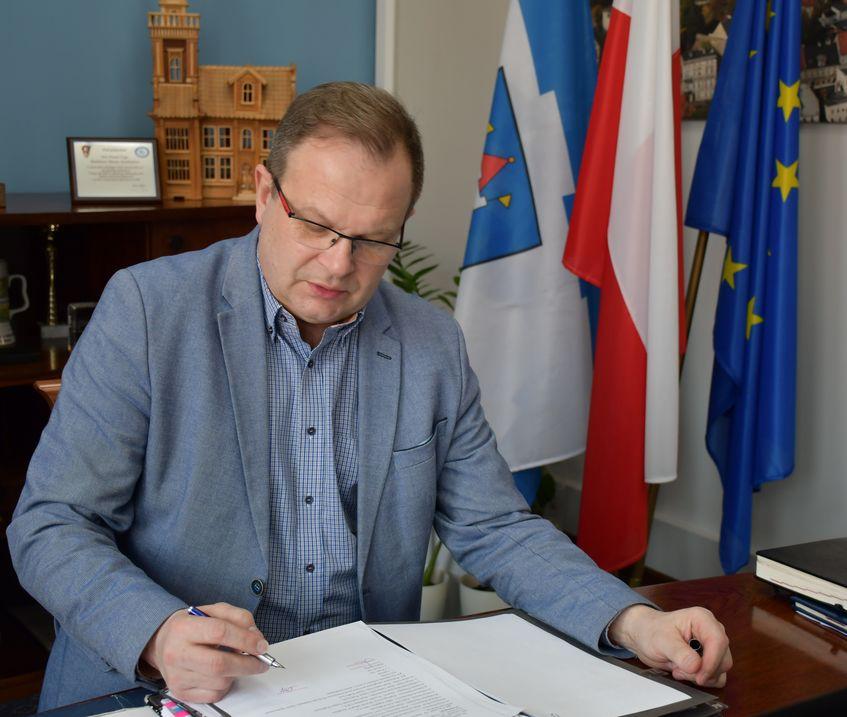 Na zdjęciu widać burmistrza miasta siedzącego przy biurku, czytającego dokument.