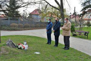 Trzy osoby stojące przed tablicą pamiątkową w Parku Miejskim