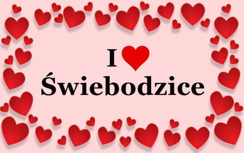 Poziomy prostokąt z różowym tłem , na środku napis I love Świebodzice w kolorze czarnym otoczony  czerwonymi sercami.