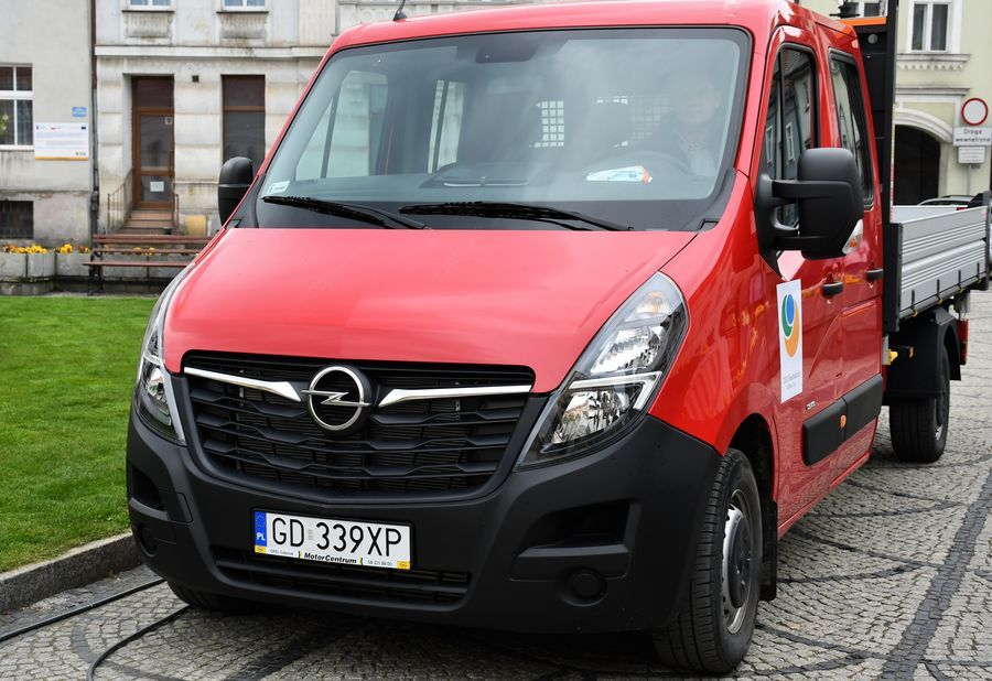 Na zdjęciu widoczne jest czerwone auto zaparkowane na tle białego budynku