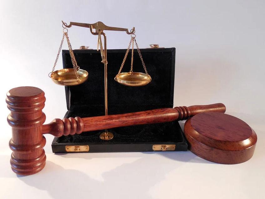 Na zdjęciu widoczne atrybuty sądownictwa: waga, młotek.