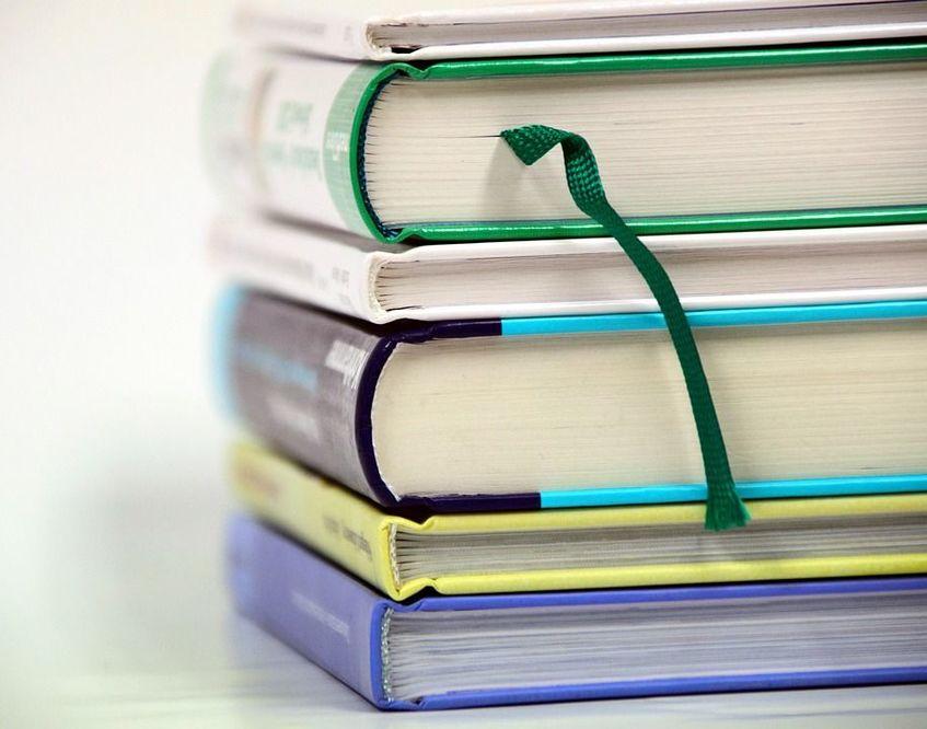 Pięć książek ułożonych jedna na drugiej.