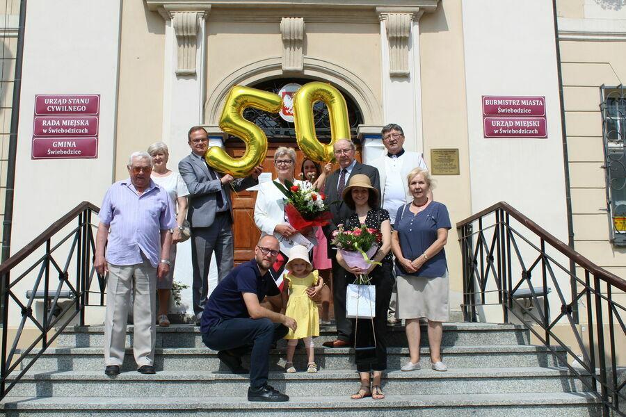 Zdjęcie przedstawia Jubilatów z Burmistrzem Miasta Pawłem Ozgą i rodziną stojących na schodach przed Ratuszem.