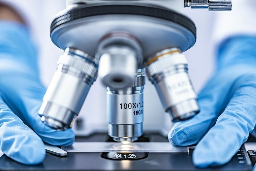 Na zdjęciu widoczny mikroskop i dłonie w niebieskich rękawiczkach