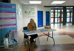 Poziomy prostokąt. Na zdjęciu widoczna kobieta siedząca przy stoliku. W tle baner akcji Szczepimy się.