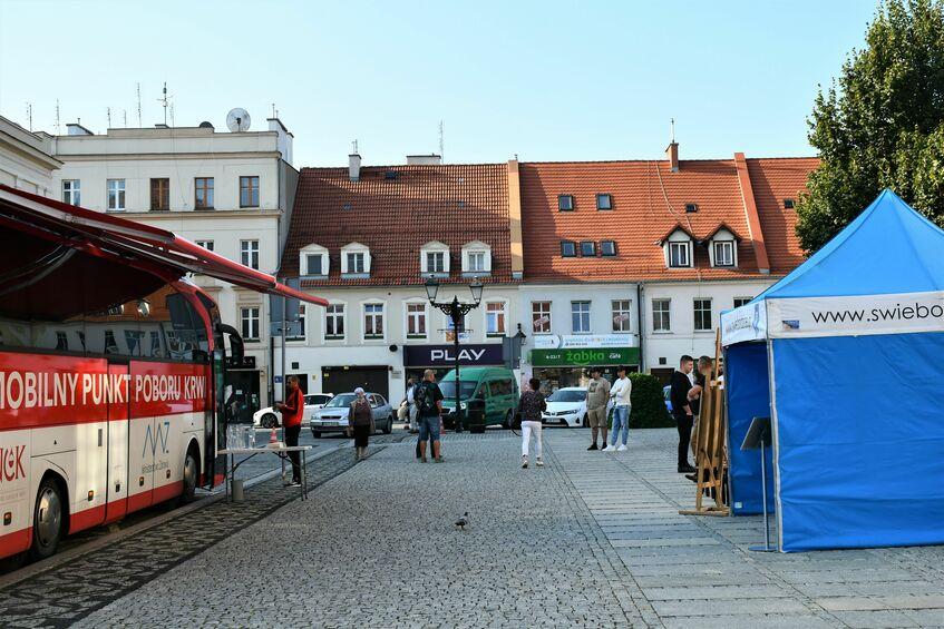 Na zdjęciu widoczny jest płyta Ratusza. Po lewej stoi mobilny punkt poboru krwi, po prawej niebiesko-biały namiot Gminy Świebodzice. Widać również oczekujących ludzi.