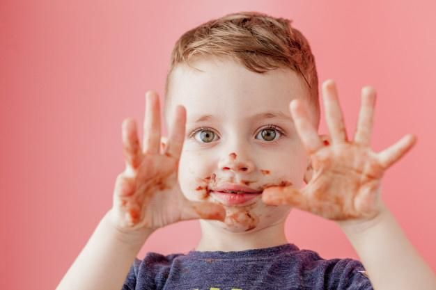 Uśmiechnięte dziecko pobrudzone jedzeniem